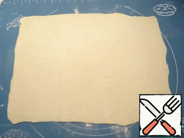 Using flour to sprinkle the table, roll out the dough into a rectangle.