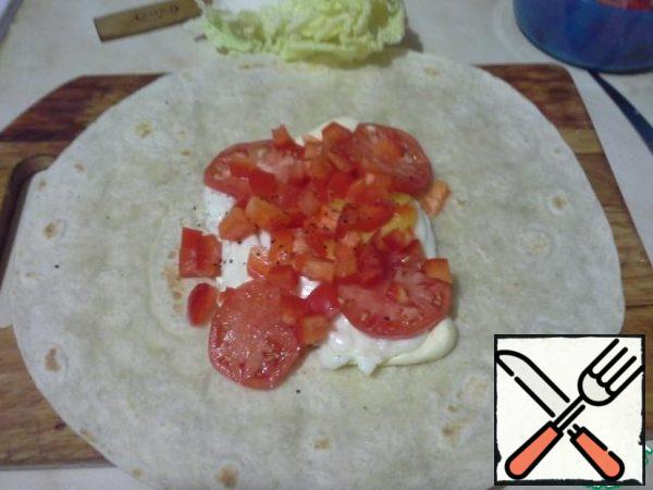 Put the peppers and tomatoes on a tortilla, lightly pepper.