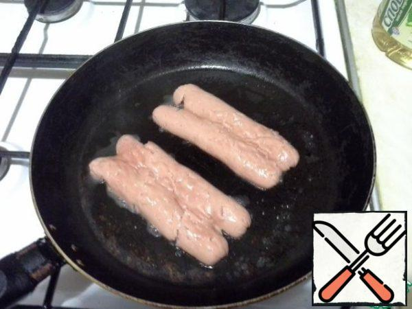 Sausages to be cut longitudinally, spread, and nailed by the hammer to sausages frying does not turns. Fry in a heated pan with the addition of vegetable oil on both sides.