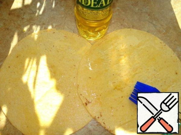 Tortilla spread on the table in overlap, grease with oil;