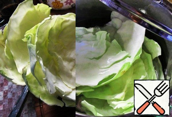 Cabbage to wash, disassemble on the leaves. If they are damaged, it's not scary. In minced add salt and spices to taste. put a pot of water on the fire, add salt, bring to a boil. Turn down the heat, put the cabbage and boil for about 8 minutes. Remove the leaves with a slotted spoon and put in a colander to glass the water.