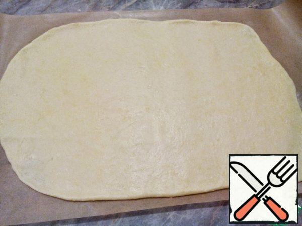 Take the baking paper the right size and lubricate with a little vegetable oil or flour. Roll out the dough on parchment paper in a thin layer.