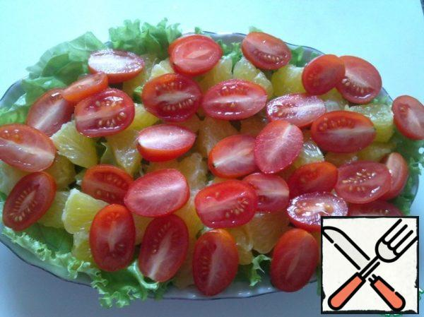 Spread the orange slices on the leaves, then put the cherry tomatoes cut in half.