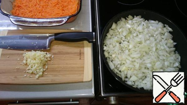 By the end of marinating carrots we need to prepare butter with onion flavor.To do this, fry the chopped onion in vegetable oil until light brown (about 15-20 minutes). At the same time finely chop the garlic (do not prohibit press).