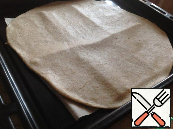The dough roll out very thinly on a working surface, sprinkled with flour. Then gently transfer to a baking sheet covered with baking paper. Of this amount of dough, make one large or two medium-sized galettes!!!