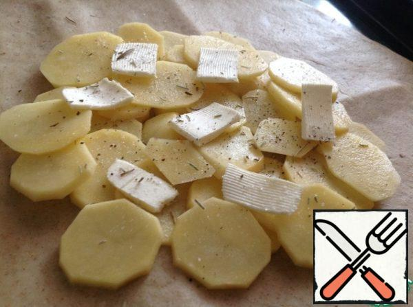 Retreating from the edge of 5 cm, lay out layers of potatoes, salt, pepper, rosemary and butter.