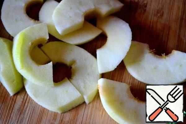 Preparing caramel apples. Clean a large Apple, remove the core and cut it with washers, divide them in half.