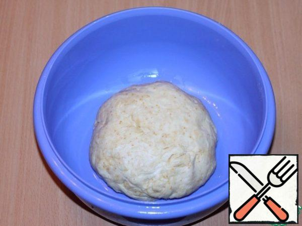 Knead the dough until it falls behind the hands. Cover the dough with a film and remove in a warm place to rise 2 times.