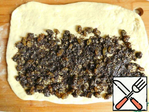 The finished dough is divided into two equal parts. One part is covered again, and the second part of the dough is rolled out (not very thin) into a rectangle. Half of the filling spread on the dough, spread evenly, not reaching the edge on one side of the rectangle.