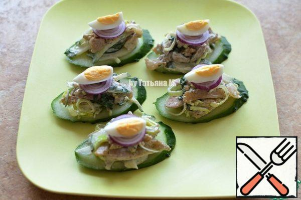 The basis of the cucumber put on a dish for serving, put on the basis of a salad with a slide, paint with red onions and a quarter of quail eggs;