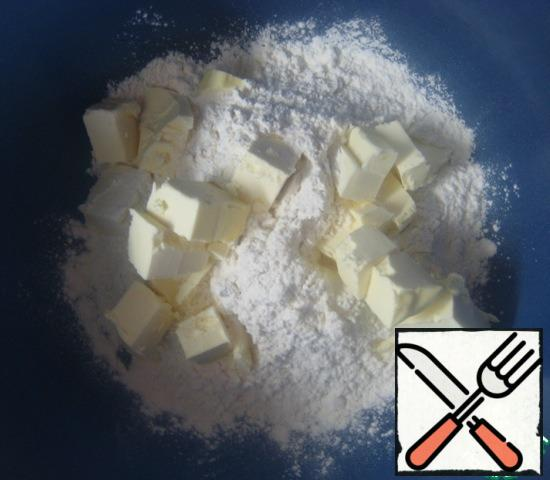 To prepare the dough butter and sour cream should be cold. Cold oil I pre-cut into cubes and still held in the freezer for 10 minutes. In a bowl combine flour and salt. Add the cold cubes of butter and quickly RUB with flour.
