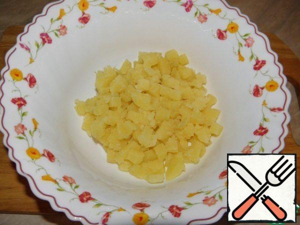 Boil potatoes, cut into cubes.