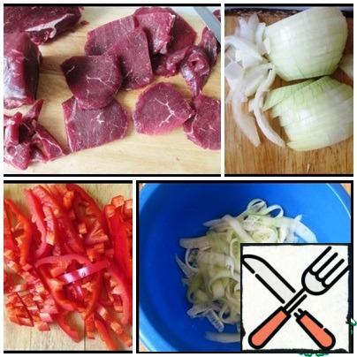 To begin, prepare the cucumber. My it and cut into thin long strips with a knife for cleaning of vegetables. Fill with salt and leave for 15 minutes Beef cut along the fibers into thin slices, better cut slightly frozen beef, and then cut across the fibers into thin ribbons. Onions shinkuem thin half-rings, pepper cut into strips.