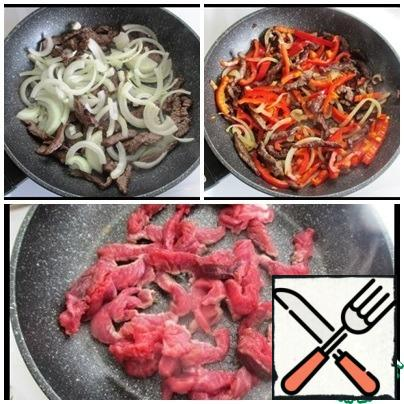 On a heated pan pour a little vegetable oil, spread the meat and fry until the liquid evaporates. Then add a couple of tablespoons of vegetable oil, spread the onion and fry, stirring, 1-2 minutes. Add the strips of pepper, pour the soy sauce and fry for another 2 minutes. Remove from heat, cover with a lid.