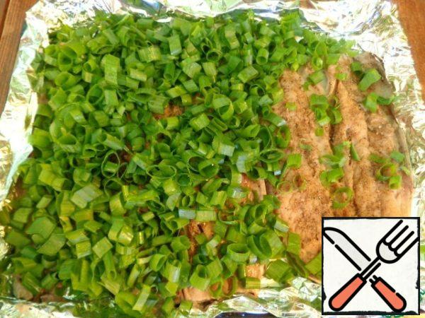 Heat oven to 180 degrees. Green onion cut into rings. Lay the baking sheet with foil, grease with vegetable oil. Put the mackerel fillet on a baking sheet and cover with a layer of green onions.