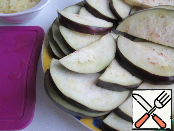 Slices of eggplant get wet with a paper towel.