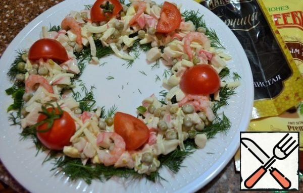 Spread the salad over the dill. Lay out shrimps, sliced tomatoes.