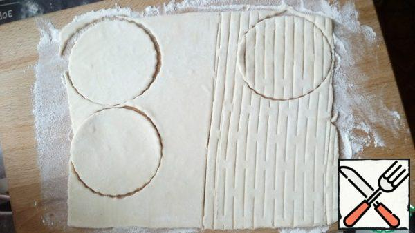 Roll out the dough and cut 4 cups with a round notch. In the second half of the test walk roller for cutting bars, cut another 4 mug. If there is no roller, it is possible to make a knife several parallel cuts on the cut out circle, without reaching the edges of the dough.