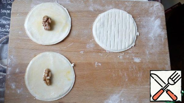 Dough 4 circles grease with yolk, sprinkle with powdered sugar. Put half or quarter of the nut.