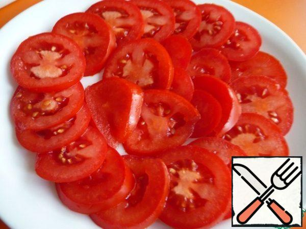 Tomatoes cut into rings (half-rings), spread on a plate.