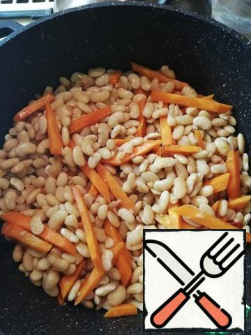 To carrots add beans (without water), finely chopped garlic, 1.5 cups of juice (or tomato paste diluted with water). The remaining juice is left aside to wait in the wings. Salt the beans and add the sugar. Simmer under the lid for about 20 minutes, stirring occasionally.