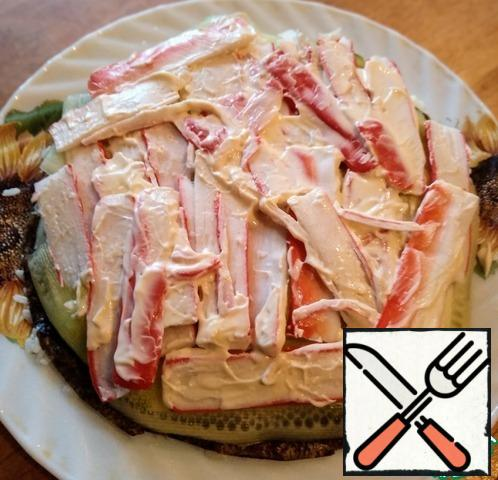 Crab sticks cut into strips, spread on cucumber and grease with mayonnaise. On top of the nori sheet, cut as the first.