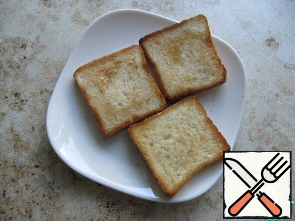 Slices of toast bread to dry in a frying pan on both sides with the addition of a small amount of vegetable oil.
