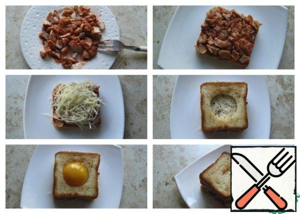 If cutting fillet is large, the cooled pieces of meat to disassemble the plug on the fiber. Put the chopped chicken fillet with ketchup on a slice of toast. Put a layer of grated hard cheese on top. From above cover with a slice of bread, in which proactively on center cut a glass hole. Pour the yolk into the cut hole. Cover with a slice of bread from above.