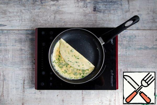 Without removing from the heat, tilt the pan so that most of the egg mass moves to the bottom of the pan. Carefully poddevaya thin egg film, wrap it in half an omelet.