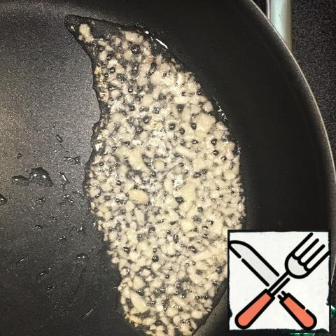 Collect our dish.In the pan pour 2 tablespoons of vegetable oil, put the fire on the maximum, warm the pan, spread finely chopped garlic, fry a little for 1-2 minutes.