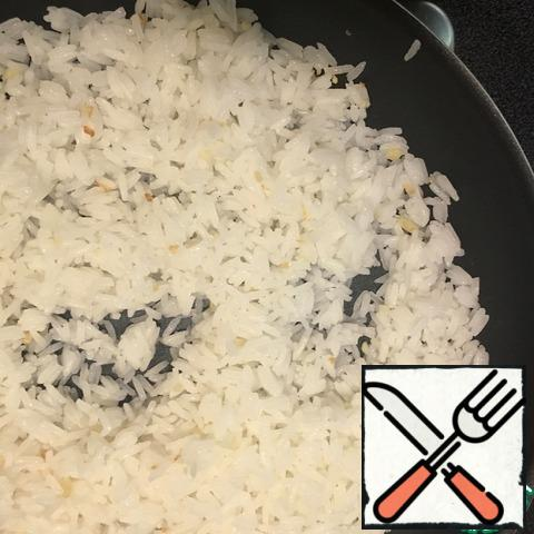 Add the boiled rice to the garlic, stir gently, fry on maximum heat for 5 minutes, fry the rice.