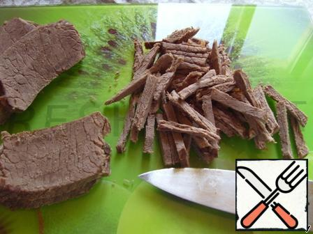 Cut boiled beef into strips.