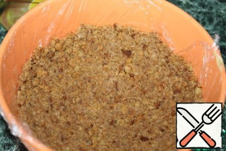 In a bowl stelem food film or paper and spread evenly oily mixture of cookies, distributing on the bottom, making the bumpers. Put it in the fridge.