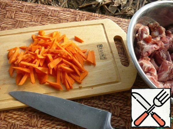 We make a fire and while it burns, cut large cubes of carrots.