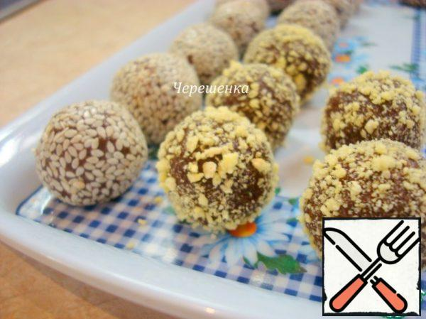 Wrap the edges of the cake to the center and roll the ball again. Then some of them are rolled in sesame seeds, the rest in crushed corn flakes. Refrigerate for 1-2 hours.