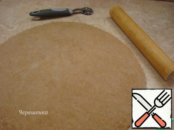 Sprinkle the table with wheat flour, roll out the dough with a diameter of about 40cm, a thickness of about 5mm.If you want to bring beauty, then cut the dough along the edges with a curly pizza knife, using a large plate to make the circle smooth. Put the circle of dough on a baking sheet, covered with parchment... I have a silicone Mat, but then I regretted that I did not take the parchment, because it is then easier to transfer the galette to the dish…
