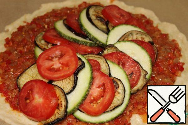 Lay out, alternating, slices of vegetables on the sauce so that they form a spiral - from the middle to the edges of the dough.