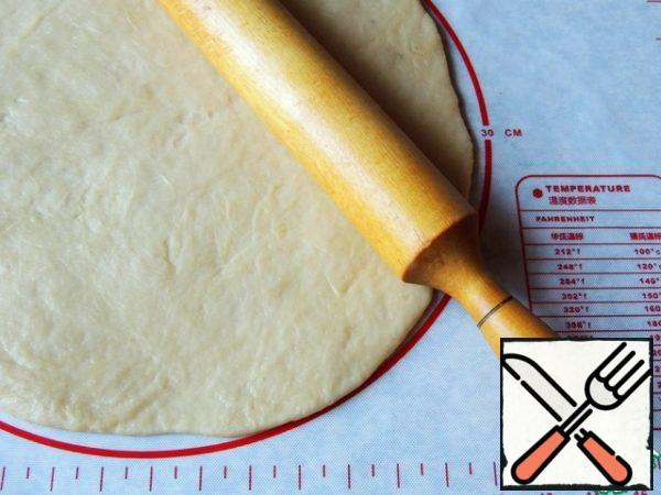 Roll out the dough to a diameter of 30 cm, trying to make the edges thinner. Further, the cake can be formed directly on the parchment (the galette assumes a free form). I made a cake in a silicone mold with a diameter of 24 cm.