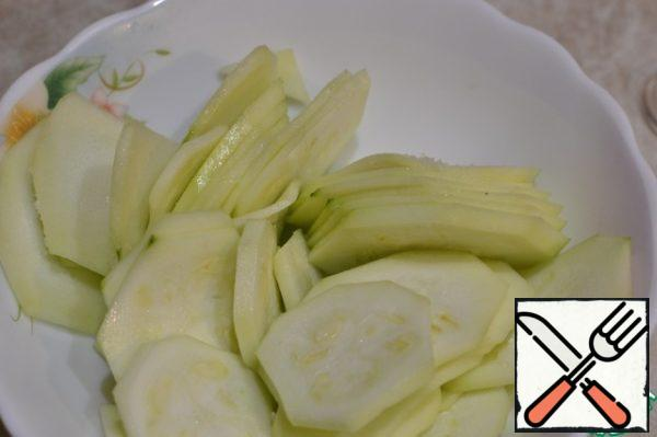 Clean the zucchini from the skin, cut into thin circles, lightly salt, sprinkle with a universal seasoning.