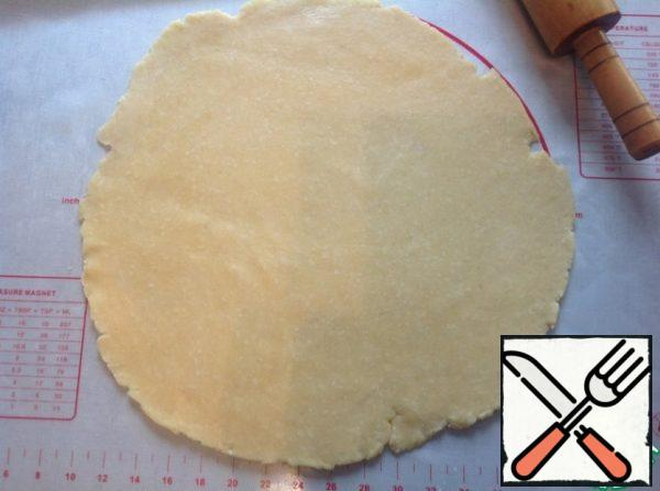 The cooled dough is rolled out on a lightly floured surface in a circle with a diameter of 35-40 cm. Transfer to the baking sheet laid with parchment. To the cake is not broken, I roll out on a large silicone Mat, then put on top of the baking sheet, covered with parchment and turn over with a silicone Mat.