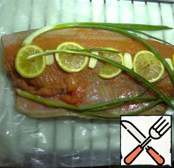 Wet the baking paper - put the trout fillet on it. Season with salt and pepper, put slices of lemon, and green onions.