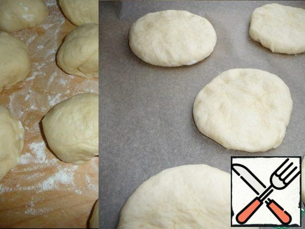 The dough is divided into 10 parts of 76.5 g, round them and leave alone for 10 minutes under the film, then crush the dough with a flat cake and put on a baking sheet, covered with baking paper, at a distance from each other, cover with a film and leave for 15 minutes to rise.