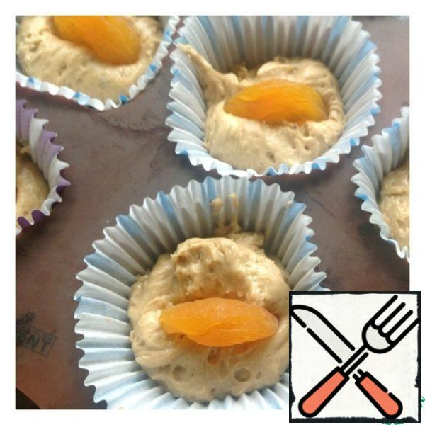 Put the dough into molds. Dried apricots are not pre-soaked. 1 thing dried apricots inserted in the center cupcakes until the end of the molds. Send cupcakes in the oven at 180 degrees until tender ( 15-20 minutes).