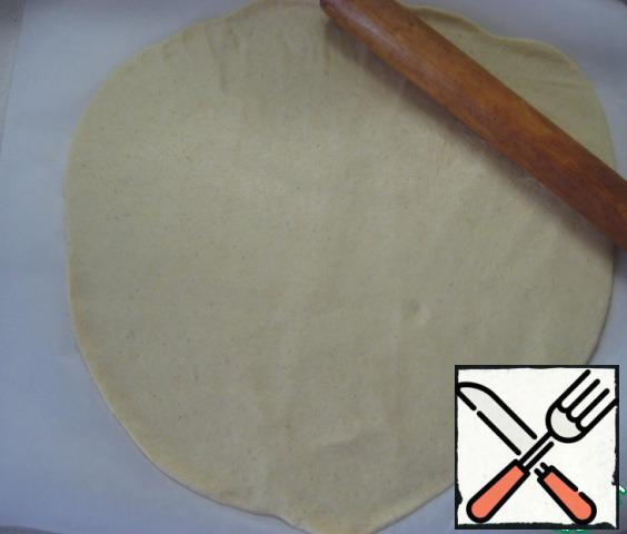Roll out the dough thinly on a sheet of baking paper.