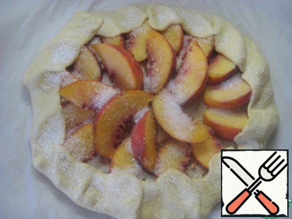 Wrap the edges of the galette on top of peaches. Slightly sprinkle water on the edges of the dough and sprinkle with sugar.