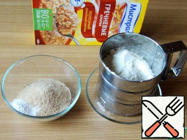 Buckwheat flakes grind in a coffee grinder to a state of flour. Mix and sift buckwheat and wheat flour and soda.