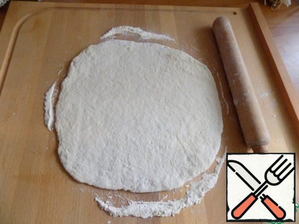 Roll out a layer of about 0.7-1 cm. I use a pizza mold for baking D-24 cm. Here is the same diameter and I roll out the dough.