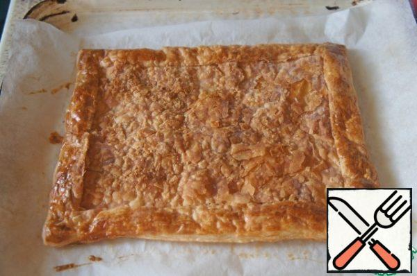 Place the dough on the parchment, grease the edges with beaten egg and transfer to a baking sheet. Bake for 15 minutes. To get the cake from oven and slightly flatten the middle, keeping the side is high.