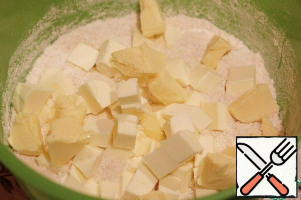 Butter cut into cubes, add it to the dry mixture and grind your fingers into crumbs or chop with a knife. Do not do it too carefully, it will be even better if the dough will remain small pieces of butter.
