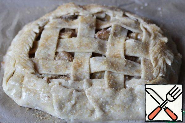 Remove the Galette from the freezer and, if it was on a cutting Board, place it on a baking sheet covered with baking paper. Grease the edges of the biscuits and the surface of the braid with egg mixture and sprinkle with cane sugar.